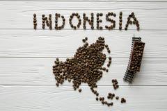 Χάρτης της Ινδονησίας φιαγμένης από ψημένα φασόλια καφέ που βάζουν στο άσπρο ξύλινο κατασκευασμένο υπόβαθρο με το τραίνο παιχνιδι Στοκ φωτογραφία με δικαίωμα ελεύθερης χρήσης