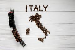 Χάρτης της Ιταλίας φιαγμένης από ψημένα φασόλια καφέ που βάζουν στο άσπρο ξύλινο κατασκευασμένο υπόβαθρο με το τραίνο παιχνιδιών Στοκ Εικόνα