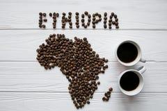 Χάρτης της Κένυας φιαγμένης από ψημένα φασόλια καφέ που βάζουν στο άσπρο ξύλινο κατασκευασμένο υπόβαθρο με δύο φλιτζάνια του καφέ Στοκ Εικόνες