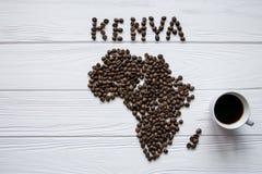 Χάρτης της Κένυας φιαγμένης από ψημένα φασόλια καφέ που βάζουν στο άσπρο ξύλινο κατασκευασμένο υπόβαθρο με το φλιτζάνι του καφέ Στοκ εικόνες με δικαίωμα ελεύθερης χρήσης