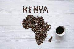 Χάρτης της Κένυας φιαγμένης από ψημένα φασόλια καφέ που βάζουν στο άσπρο ξύλινο κατασκευασμένο υπόβαθρο με το φλιτζάνι του καφέ Στοκ φωτογραφία με δικαίωμα ελεύθερης χρήσης