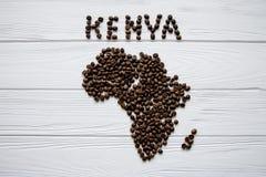 Χάρτης της Κένυας φιαγμένης από ψημένα φασόλια καφέ που βάζουν στο άσπρο ξύλινο κατασκευασμένο υπόβαθρο Στοκ Εικόνα