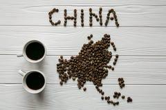 Χάρτης της Κίνας φιαγμένης από ψημένα φασόλια καφέ που βάζουν στο άσπρο ξύλινο κατασκευασμένο υπόβαθρο με δύο φλιτζάνια του καφέ Στοκ Φωτογραφίες