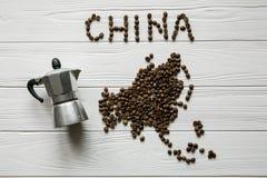 Χάρτης της Κίνας φιαγμένης από ψημένα φασόλια καφέ που βάζουν στο άσπρο ξύλινο κατασκευασμένο υπόβαθρο με τον κατασκευαστή καφέ Στοκ φωτογραφίες με δικαίωμα ελεύθερης χρήσης