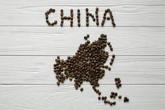 Χάρτης της Κίνας φιαγμένης από ψημένα φασόλια καφέ που βάζουν στο άσπρο ξύλινο κατασκευασμένο υπόβαθρο Στοκ Εικόνες