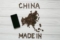 Χάρτης της Κίνας φιαγμένης από ψημένα φασόλια καφέ που βάζουν στο άσπρο ξύλινο κατασκευασμένο υπόβαθρο με το τηλέφωνο Στοκ Εικόνες