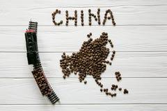 Χάρτης της Κίνας φιαγμένης από ψημένα φασόλια καφέ που βάζουν στο άσπρο ξύλινο κατασκευασμένο υπόβαθρο με το τραίνο παιχνιδιών Στοκ φωτογραφία με δικαίωμα ελεύθερης χρήσης