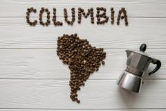 Χάρτης της Κολούμπια φιαγμένης από ψημένα φασόλια καφέ που βάζουν στο άσπρο ξύλινο κατασκευασμένο υπόβαθρο με τον κατασκευαστή κα Στοκ εικόνες με δικαίωμα ελεύθερης χρήσης