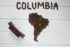 Χάρτης της Κολούμπια φιαγμένης από ψημένα φασόλια καφέ που βάζουν στο άσπρο ξύλινο κατασκευασμένο τραίνο παιχνιδιών υποβάθρου Στοκ Εικόνες