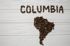 Χάρτης της Κολούμπια φιαγμένης από ψημένα φασόλια καφέ που βάζουν στο άσπρο ξύλινο κατασκευασμένο υπόβαθρο Στοκ Εικόνες
