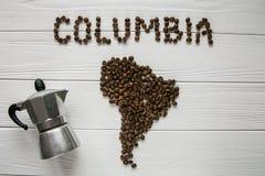 Χάρτης της Κολούμπια φιαγμένης από ψημένα φασόλια καφέ που βάζουν στο άσπρο ξύλινο κατασκευασμένο υπόβαθρο με τον κατασκευαστή κα Στοκ Εικόνα