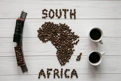 Χάρτης της Νότιας Αφρικής φιαγμένης από ψημένα φασόλια καφέ που βάζουν στο άσπρο ξύλινο κατασκευασμένο υπόβαθρο με δύο φλιτζάνια  Στοκ Εικόνα