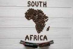 Χάρτης της Νότιας Αφρικής φιαγμένης από ψημένα φασόλια καφέ που βάζουν στο άσπρο ξύλινο κατασκευασμένο υπόβαθρο με το τραίνο παιχ Στοκ εικόνα με δικαίωμα ελεύθερης χρήσης