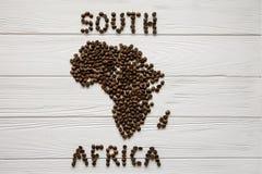 Χάρτης της Νότιας Αφρικής φιαγμένης από ψημένα φασόλια καφέ που βάζουν στο άσπρο ξύλινο κατασκευασμένο υπόβαθρο Στοκ Φωτογραφία