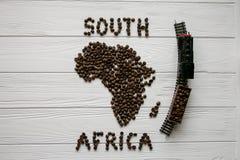 Χάρτης της Νότιας Αφρικής φιαγμένης από ψημένα φασόλια καφέ που βάζουν στο άσπρο ξύλινο κατασκευασμένο υπόβαθρο με το τραίνο παιχ Στοκ φωτογραφία με δικαίωμα ελεύθερης χρήσης