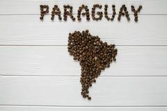 Χάρτης της Παραγουάης φιαγμένης από ψημένα φασόλια καφέ που βάζουν στο άσπρο ξύλινο κατασκευασμένο υπόβαθρο Στοκ Εικόνα