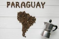 Χάρτης της Παραγουάης φιαγμένης από ψημένα φασόλια καφέ που βάζουν στο άσπρο ξύλινο κατασκευασμένο υπόβαθρο με τον κατασκευαστή κ Στοκ Φωτογραφίες