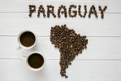 Χάρτης της Παραγουάης φιαγμένης από ψημένα φασόλια καφέ που βάζουν στο άσπρο ξύλινο κατασκευασμένο υπόβαθρο με δύο φλιτζάνια του  Στοκ Φωτογραφία