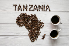 Χάρτης της Τανζανίας φιαγμένης από ψημένα φασόλια καφέ που βάζουν στο άσπρο ξύλινο κατασκευασμένο υπόβαθρο με δύο φλυτζάνια καφέ Στοκ εικόνες με δικαίωμα ελεύθερης χρήσης