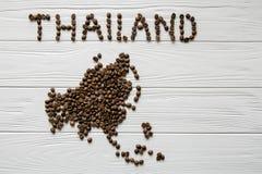Χάρτης της Ταϊλάνδης φιαγμένης από ψημένα φασόλια καφέ που βάζουν στο άσπρο ξύλινο κατασκευασμένο υπόβαθρο Στοκ Εικόνες