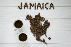 Χάρτης της Τζαμάικας φιαγμένης από ψημένα φασόλια καφέ που βάζουν στο άσπρο ξύλινο κατασκευασμένο υπόβαθρο με δύο φλιτζάνια του κ Στοκ Εικόνα