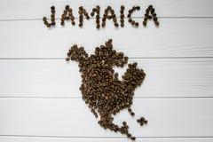Χάρτης της Τζαμάικας φιαγμένης από ψημένα φασόλια καφέ που βάζουν στο άσπρο ξύλινο κατασκευασμένο υπόβαθρο Στοκ Φωτογραφίες