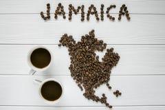 Χάρτης της Τζαμάικας φιαγμένης από ψημένα φασόλια καφέ που βάζουν στο άσπρο ξύλινο κατασκευασμένο υπόβαθρο με δύο φλιτζάνια του κ Στοκ εικόνα με δικαίωμα ελεύθερης χρήσης