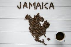 Χάρτης της Τζαμάικας φιαγμένης από ψημένα φασόλια καφέ που βάζουν στο άσπρο ξύλινο κατασκευασμένο υπόβαθρο με το φλιτζάνι του καφ Στοκ Φωτογραφία