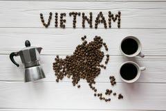 Χάρτης του Βιετνάμ φιαγμένου από ψημένα φασόλια καφέ που βάζουν στο άσπρο ξύλινο κατασκευασμένο υπόβαθρο με τον κατασκευαστή καφέ Στοκ εικόνες με δικαίωμα ελεύθερης χρήσης