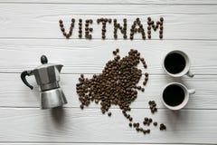 Χάρτης του Βιετνάμ φιαγμένου από ψημένα φασόλια καφέ που βάζουν στο άσπρο ξύλινο κατασκευασμένο υπόβαθρο με τον κατασκευαστή καφέ Στοκ Φωτογραφία