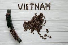 Χάρτης του Βιετνάμ φιαγμένου από ψημένα φασόλια καφέ που βάζουν στο άσπρο ξύλινο κατασκευασμένο υπόβαθρο με το τραίνο παιχνιδιών Στοκ φωτογραφία με δικαίωμα ελεύθερης χρήσης