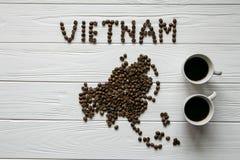 Χάρτης του Βιετνάμ φιαγμένου από ψημένα φασόλια καφέ που βάζουν στο άσπρο ξύλινο κατασκευασμένο υπόβαθρο με δύο φλιτζάνια του καφ Στοκ Φωτογραφία