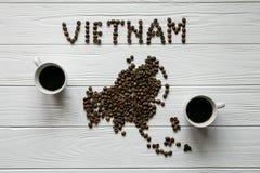 Χάρτης του Βιετνάμ φιαγμένου από ψημένα φασόλια καφέ που βάζουν στο άσπρο ξύλινο κατασκευασμένο υπόβαθρο με δύο φλιτζάνια του καφ Στοκ εικόνες με δικαίωμα ελεύθερης χρήσης