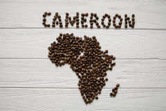 Χάρτης του Καμερούν φιαγμένου από ψημένα φασόλια καφέ που βάζουν στο άσπρο ξύλινο κατασκευασμένο υπόβαθρο Στοκ Φωτογραφία