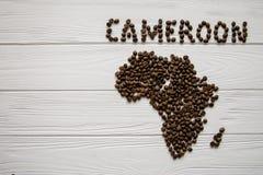 Χάρτης του Καμερούν φιαγμένου από ψημένα φασόλια καφέ που βάζουν στο άσπρο ξύλινο κατασκευασμένο υπόβαθρο Στοκ εικόνες με δικαίωμα ελεύθερης χρήσης