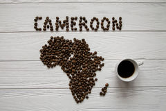 Χάρτης του Καμερούν φιαγμένου από ψημένα φασόλια καφέ layin στο άσπρο ξύλινο κατασκευασμένο υπόβαθρο με το φλυτζάνι καφέ Στοκ Εικόνες