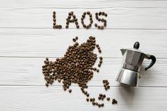 Χάρτης του Λάος φιαγμένου από ψημένα φασόλια καφέ που βάζουν στο άσπρο ξύλινο κατασκευασμένο υπόβαθρο με τον κατασκευαστή καφέ Στοκ εικόνες με δικαίωμα ελεύθερης χρήσης