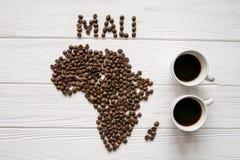 Χάρτης του Μαλί φιαγμένου από ψημένα φασόλια καφέ που βάζουν στο άσπρο ξύλινο κατασκευασμένο υπόβαθρο με δύο φλιτζάνια του καφέ Στοκ φωτογραφία με δικαίωμα ελεύθερης χρήσης