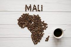 Χάρτης του Μαλί φιαγμένου από ψημένα φασόλια καφέ που βάζουν στο άσπρο ξύλινο κατασκευασμένο υπόβαθρο με το φλιτζάνι του καφέ Στοκ φωτογραφία με δικαίωμα ελεύθερης χρήσης