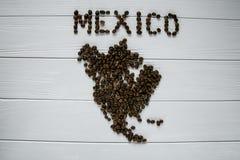 Χάρτης του Μεξικού φιαγμένου από ψημένα φασόλια καφέ που βάζουν στο άσπρο ξύλινο κατασκευασμένο υπόβαθρο Στοκ Εικόνες
