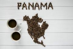 Χάρτης του Παναμά φιαγμένου από ψημένα φασόλια καφέ που βάζουν στο άσπρο ξύλινο κατασκευασμένο υπόβαθρο με δύο φλιτζάνια του καφέ Στοκ Εικόνα