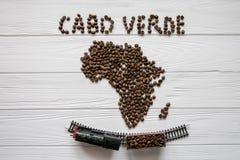 Χάρτης του Cabo Verde φιαγμένο από ψημένα φασόλια καφέ που βάζουν στο άσπρο ξύλινο κατασκευασμένο υπόβαθρο με το τραίνο παιχνιδιώ Στοκ φωτογραφία με δικαίωμα ελεύθερης χρήσης
