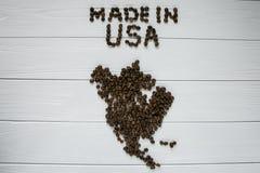 Χάρτης των ΗΠΑ φιαγμένων από ψημένα φασόλια καφέ που βάζουν στο άσπρο ξύλινο κατασκευασμένο υπόβαθρο Στοκ Εικόνα