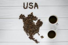 Χάρτης των ΗΠΑ φιαγμένων από ψημένα φασόλια καφέ που βάζουν στο άσπρο ξύλινο κατασκευασμένο υπόβαθρο με δύο φλιτζάνια του καφέ Στοκ φωτογραφίες με δικαίωμα ελεύθερης χρήσης