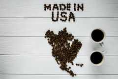 Χάρτης των ΗΠΑ φιαγμένων από ψημένα φασόλια καφέ που βάζουν στο άσπρο ξύλινο κατασκευασμένο υπόβαθρο με δύο φλιτζάνια του καφέ Στοκ εικόνες με δικαίωμα ελεύθερης χρήσης