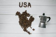 Χάρτης των ΗΠΑ φιαγμένων από ψημένα φασόλια καφέ που βάζουν στο άσπρο ξύλινο κατασκευασμένο υπόβαθρο με τον κατασκευαστή καφέ Στοκ εικόνες με δικαίωμα ελεύθερης χρήσης