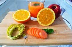 Χάστε το βάρος, τους νωπούς καρπούς και ένα ποτήρι του χυμού από πορτοκάλι σε έναν ξύλινο πίνακα στοκ εικόνες