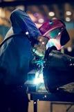 Χάλυβας συγκόλλησης υπαλλήλων με τους σπινθήρες που χρησιμοποιούν mig MAG τον οξυγονοκολλητή Στοκ Φωτογραφίες