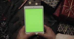 Χέρια Άγιου Βασίλη που κρατά τον άσπρο υπολογιστή ταμπλετών με την πράσινη οθόνη Άλλα χέρια που τοποθετούν μερικά παρόντα πεδία απόθεμα βίντεο