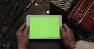 Χέρια Άγιου Βασίλη που κρατά τον άσπρο υπολογιστή ταμπλετών με την πράσινη οθόνη Άλλα χέρια που τοποθετούν μερικά παρόντα πεδία φιλμ μικρού μήκους